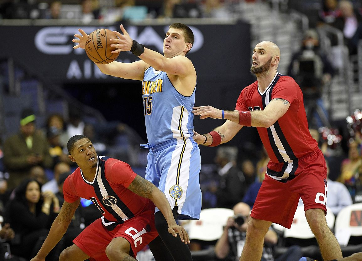 /Denver Nuggets forward Nikola Jokic, of Serbia, (15) grabs the ball against Washington Wizards center Marcin Gortat, of Poland, right, and guard Bradley Beal, lower left, during the second half of an NBA basketball game, Thursday, Dec. 8, 2016, in Washington. The Wizards won 92-85. (AP Photo/Nick Wass)
