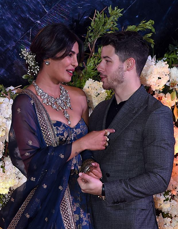 Indian Bollywood actress Priyanka Chopra (L) and US musician Nick Jonas, who were recently married, look at each other as they pose for a picture during a reception in Mumbai, India, on December 19, 2018. - Bollywood actress Priyanka Chopra and American singer Nick Jonas hosted an extravagant concert on December 2, 2019, for their star-studded wedding guests as the couple tied the knot at a lavish Indian palace. (Photo by Sujit Jaiswal / AFP)