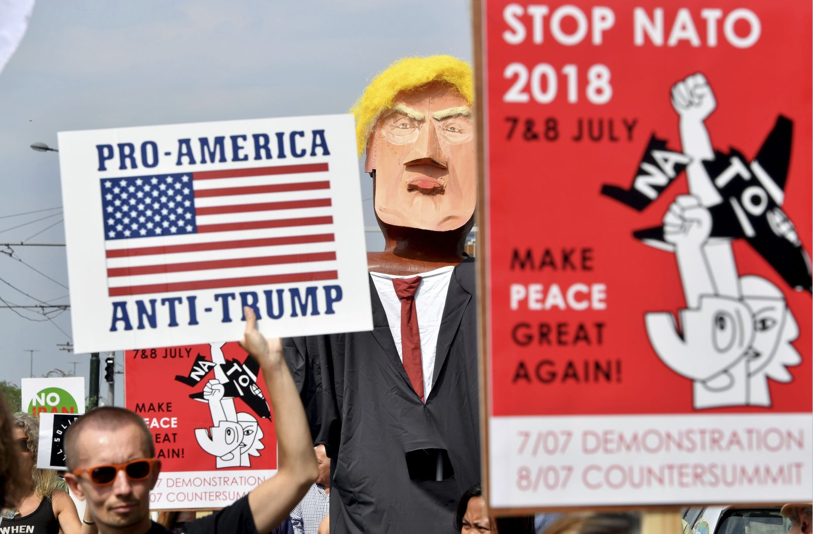 A protestor marches next to giant puppet of U.S. President Donald Trump, right, as he holds a sign which reads Pro-America, Anti-Trump during a demonstration in Brussels, Saturday, July 7, 2018. European activists are protesting U.S. President Donald Trumps upcoming appearance at a NATO summit, marching through Brussels to plead for less military spending and more public money for schools and clean energy. (AP Photo/Geert Vanden Wijngaert)