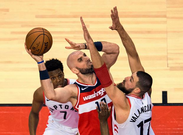 Washington Wizards center Marcin Gortat (13) drives into Toronto Raptors center Jonas Valanciunas (17) as Raptors guard Kyle Lowry (7) watches during the first half of Game 5 of an NBA basketball first-round playoff series Wednesday, April 25, 2018, in Toronto. (Nathan Denette/The Canadian Press via AP)