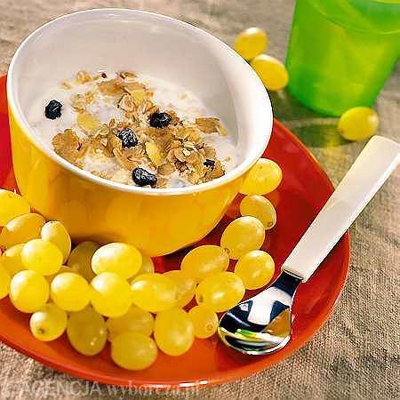 Jogurt naturalny z muesli i małymi rodzynkowymi zielonymi winogronami.