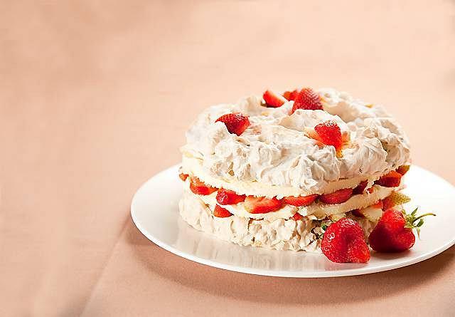 Bezowy tort orzechowy z kremem waniliowo-pomarańczowym i z truskawkami