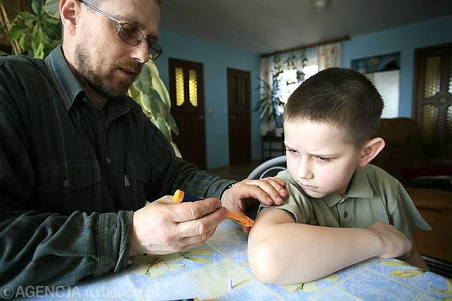 Pan Zbigniew podaje insulinę swojemu siedmioletniemu synowi Kamilowi