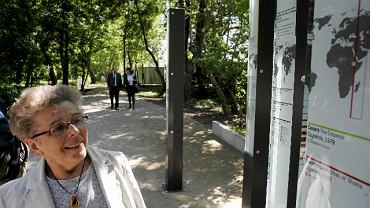 Alicja Kapuścińska przy planszach, na których na mapie świata zaznaczono miejsca opisywane przez jej męża