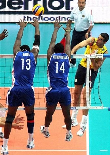 Cuba's Robertlandy Simon Aties, left, and teammate Raydel Hierrezuelo Aguirre, center, try to block a spike by Brazil's Dante Guimaraes Amaral