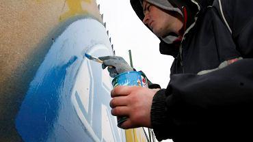 Chorzów. Remigiusz Wóz maluje logo Ruchu farbami nowego sponsora