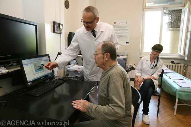 Szpital Kliniczny Dzieciątka Jezus. Dr Wojciech Glinkowski prezentuje pacjentowi Cezaremu Alifanowi zestaw ćwiczeń rehabilitacyjnych w internecie