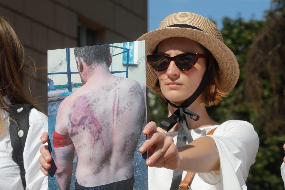 Kobieta trzyma zdjęcie pobitego przez milicję protestującego, Mińsk, 15 sierpnia 2020.