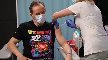 Tomasz Grodzki podczas szczepienia przeciw COVID-19 w koszulce reklamującej 29. Finał WOŚP