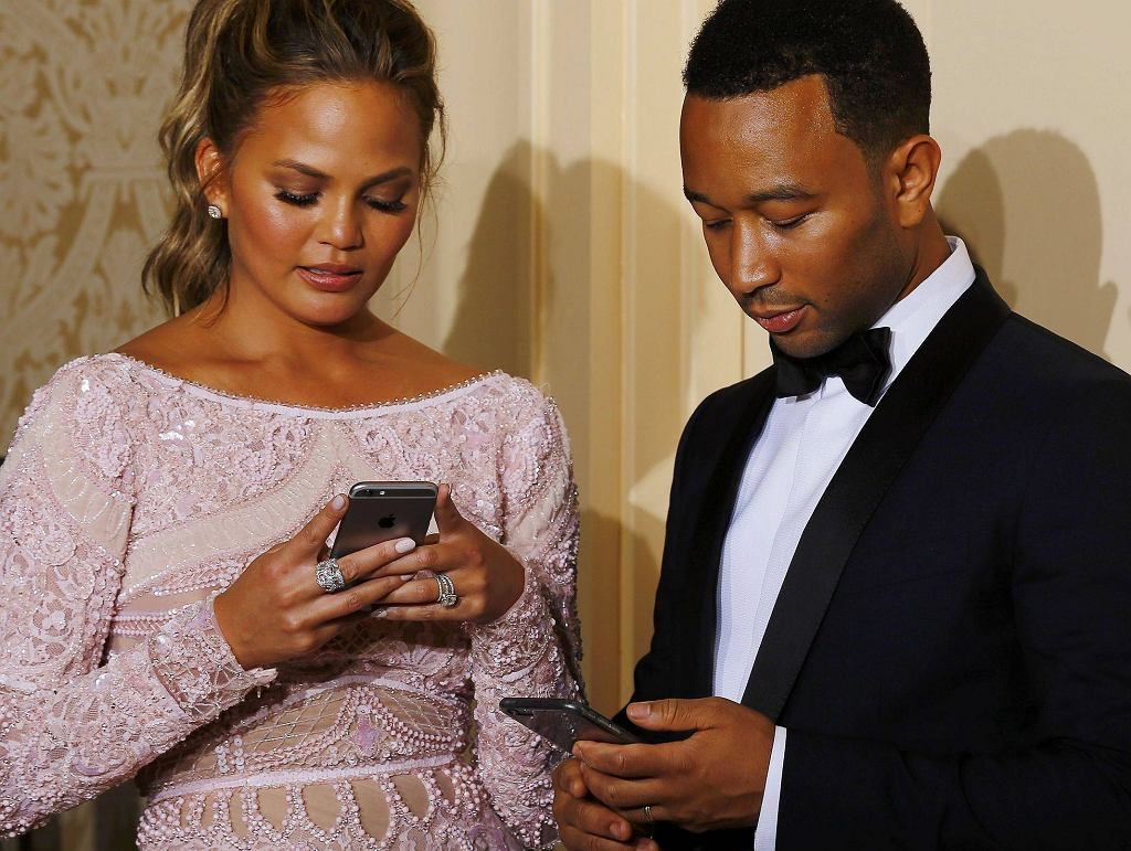 lChrissy Teigen and John Legend check their smart phones during the 72nd Golden Globe Awards in Beverly Hills