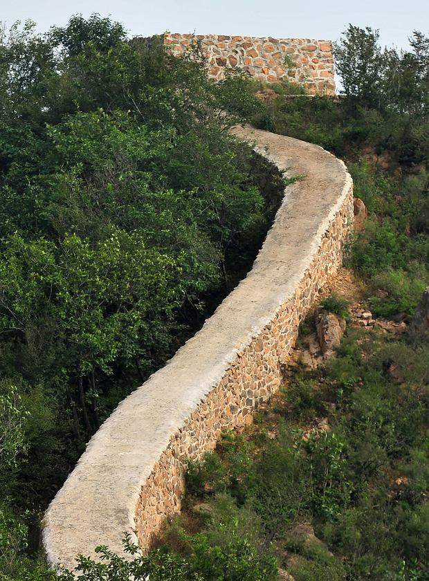 In this Wednesday, Sept. 21, 2016 photo, a restored section of the Great Wall is seen in Suizhong County in northeastern China's Liaoning Province. Chinese officials are being pilloried over the smoothing-over of a crumbling but much-loved 700-year-old section of the Great Wall of China - a UNESCO World Heritage Site - in the name of restoration. (Chinatopix via AP)