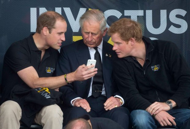 Britains Princes William (L), Charles (C) and Harry look at a mobile phone during the Invictus Games in the Lee Valley Athletics Centre in north London September 11, 2014. The Invictus Games which will run from September 10-14, is an international sporting event for wounded servicemen and women from 13 countries.   REUTERS/Neil Hall (BRITAIN - tags: SPORT - Tags: ENTERTAINMENT MILITARY SOCIETY ROYALS SPORT)