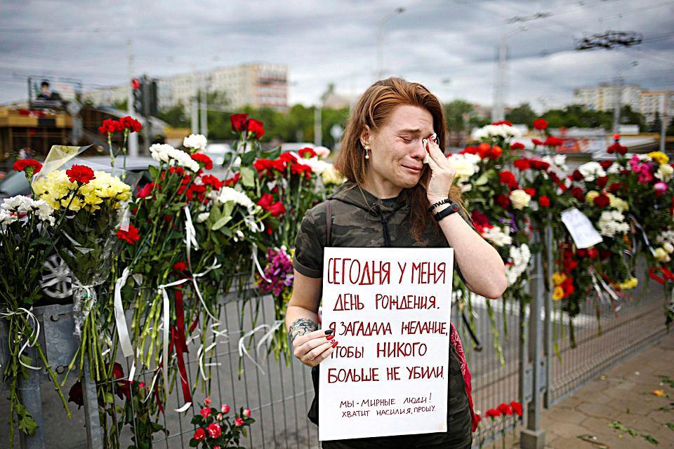 Mińsk, Białoruś. 26-letnia Alina Krus trzyma plakat w miejscu, gdzie zginął protestujący 12 sierpnia  mężczyzna. Napis: 'Dziś są moje urodziny. Ludzie. Dosyć przemocy, proszę'