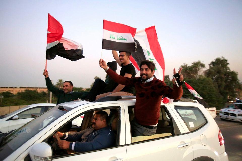 W Bagdadzie symbolicznie otwarto dla ludu Zieloną Strefę, czyli enklawę rządowo-dyplomatyczną, która  powstała wkrótce po obaleniu Saddama Husajna w 2003 r. Mieściły się tam m.in. największa na świecie ambasada USA i iracki parlament. Na zdjęciu Irakijczycy powiewają narodowymi flagami, świętując pierwszą rocznicę pokonania ISIS. Bagdad, 10 grudnia 2018 r.