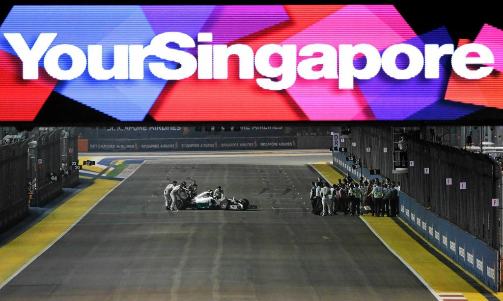 Mechanics push the car of Mercedes driver Nico Rosberg of Germany off the grid after he suffered problems with his car, just before the start of the Singapore Formula One Grand Prix on the Marina Bay City Circuit in Singapore, Sunday, Sept. 21, 2014. (AP Photo/Wong Maye-E) SLOWA KLUCZOWE: f1autoz14
