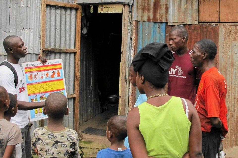 Wolontariusz informuje mieszkańców Freetown (Sierra Leone) o tym, jak można zarazić się ebolą.