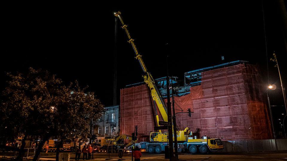Przygotowania do przeniesienia koparki nad dachem przeznaczonej do rozbiórki kamienicy