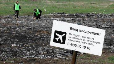 Śledczy pracują na miejscu katastrofy lotu MH17. Znak zakazuje wstępu na teren, i ostrzega, że mogą się na nim znajdować szczątki ofiar