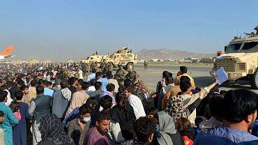 Tysiące ludzi próbują dostać się do samolotów i uciec z zajętego przez Talibów Afganistanu. Amerykańscy żołnierze utrzymują względny porządek. Kabul, 16 sierpnia 2021