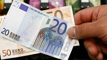 WA 20 and 50 Euro bank note are seen in front of a cash drawer with Swiss francs in Bern
