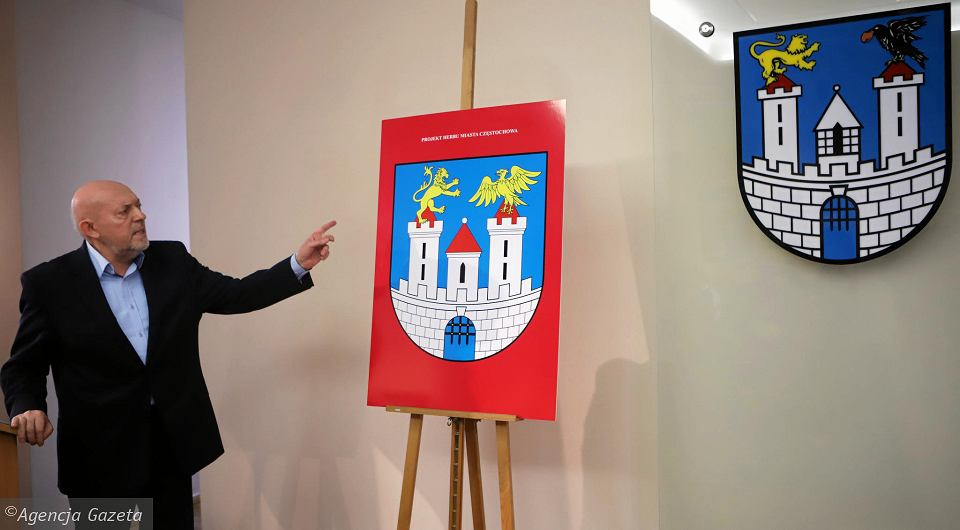 Częstochowa, ratusz, 14 grudnia 2017 r. Plastyk Andrzej Desperak pokazuje projekt nowego herbu miasta. Obok, na ścianie, obecnie obowiązujący herb