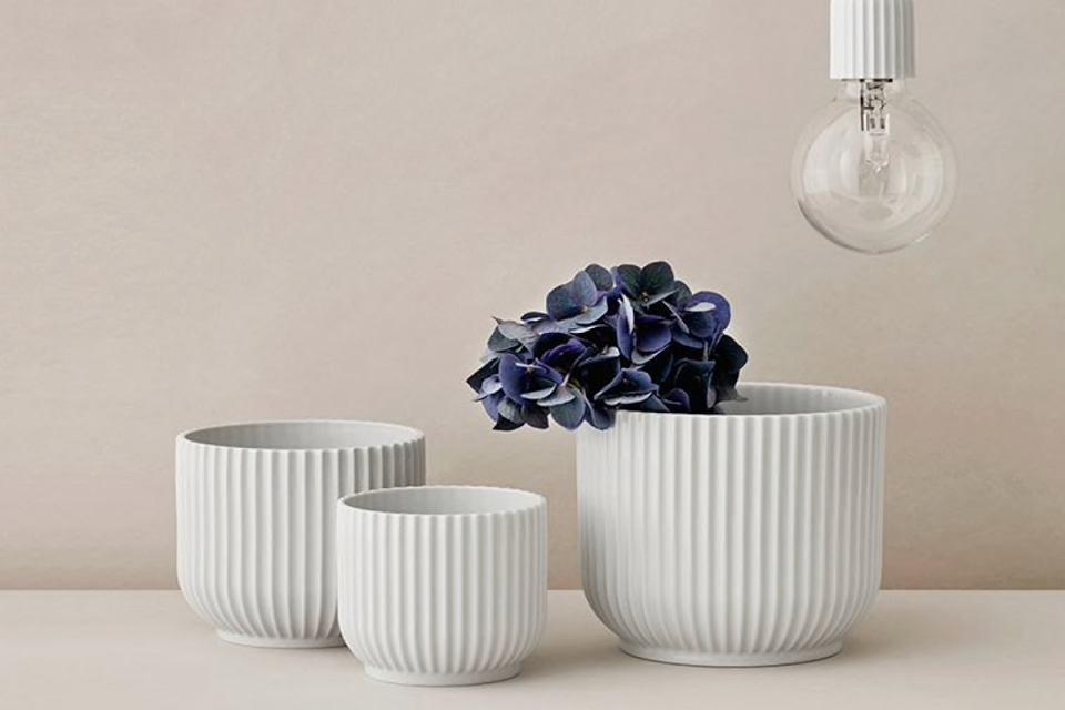 Białe donice z porcelany z charakterystycznym wzorem prążkowym.