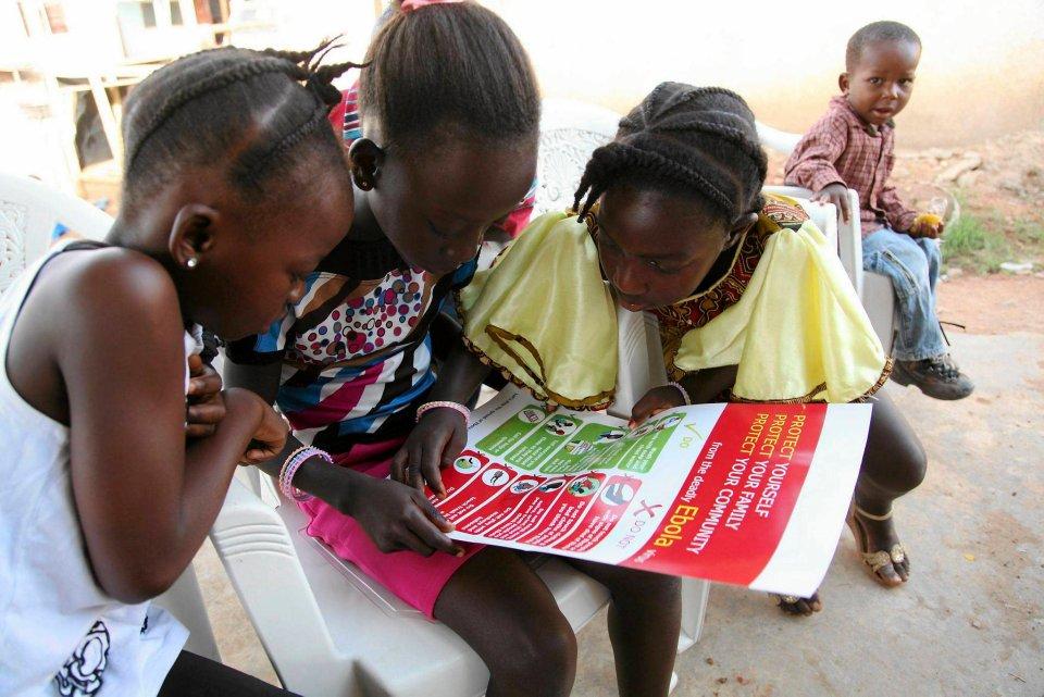 Dziewczynki oglądają plakat informacyjny przywieziony przez UNICEF.