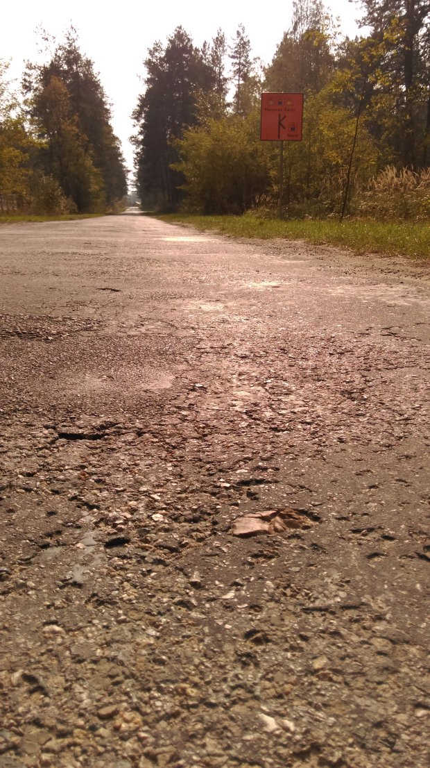 nierówny asfalt drogi wiejskiej