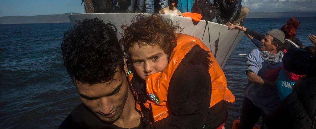 Uchodźcy wysiadają z łodzi na wyspie Lesbos