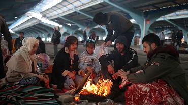 Migranci ogrzewają się przy ognisku rozpalonym na skraju targu w tureckim mieście Edirne, niedaleko granicy z Turcją, 5 marca 2020 r.