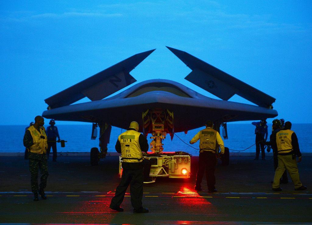Futurystycznie wyglądający X-47B podczas testów na lotniskowcu. Skrzydła są złożone w celu zmniejszenia ogólnego rozmiaru maszyny, co na ciasnym pokładzie lotniskowca ma duże znaczenie