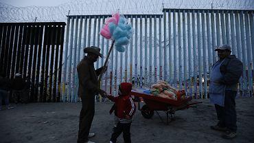 Dziecko uchodźców z Hondurasu, którzy przybyli do granicy z USA z 'karawaną imigrantów', próbuje kupić watę cukrową od ulicznego sprzedawcy, ale ma za mało pieniędzy. Tijuana, 9 grudnia 2018