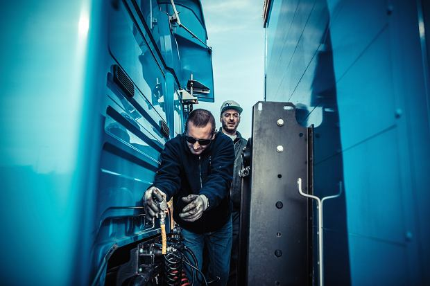 Pan Krzysztof odpina przewody łączące ciągnik z naczepą. Taka robota tylko w rękawicach.