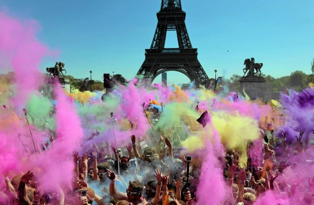 People take part in the Color Run near the Eiffel Tower, in Paris, France, Sunday, April 19, 2015. The Color Run is a 5 kilometer (3.1 mile) running event where participants are covered in bright colored powder at each check station and is less about speed and more about enjoying a day with friends and family. (AP Photo/Binta)