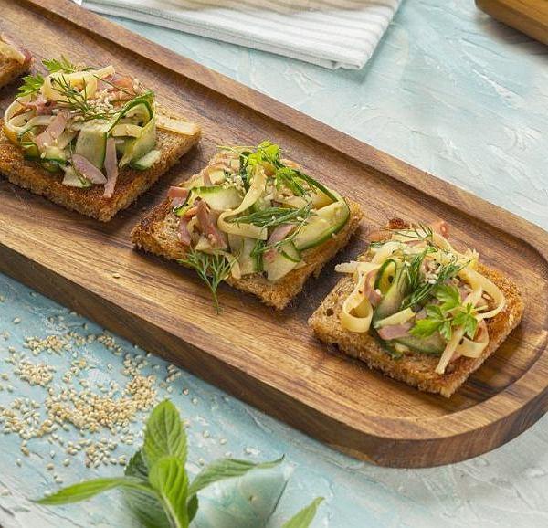 Pełnoziarniste grzanki z sałatką z szynki, sera i ogórka marynowanego.
