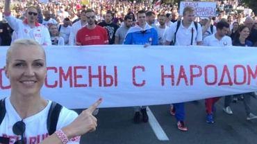 Jelena Lewczenko na marszu protestacyjnym w Mińsku. Na transparencie napis: 'Sportowcy z Narodem'