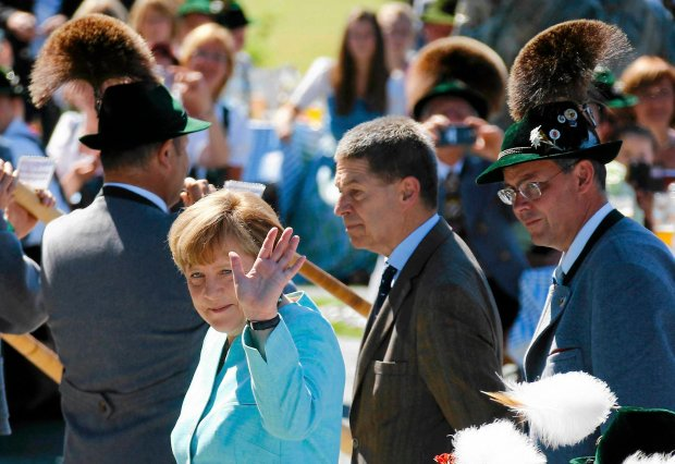German Chancellor Angela Merkel waves hand next to her husband Joachim Sauer (2nd R) before a meeting with U.S. President Barack Obama in Kruen, Germany June 7, 2015. Leaders from the Group of Seven (G7) industrial nations met on Sunday in the Bavarian Alps for a summit overshadowed by Greece's debt crisis and ongoing violence in Ukraine. REUTERS/Matthias Schrader/Pool SLOWA KLUCZOWE: :rel:d:bm:LR1EB670UNUHK