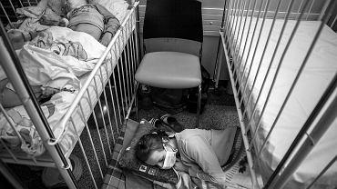 Pięciolatek unieruchomiony gipsem leży na łóżku w szpitalu dziecięcym przy ul. Szpitalnej. Patrzy w sufit i po krótkim czasie na twarzy pojawia się grymas: płacze. Nie rozumie, dlaczego jest sam. Jego rodzice obserwują go bezradnie przez podwójne szklane drzwi i korytarz. Nie mogą przytulić syna. Jest rok 1982 i odwiedziny poza wyznaczonymi dniami są zakazane. Trzydzieści trzy lata później inny chłopiec dużo lepiej znosi pobyt w tym samym szpitalu. Obok jego łóżka siedzi na krześle mama. Podaje picie, czyta książkę, pomaga przy wyjściu do ubikacji. Po prostu jest. Ale z każdą nocą traci siły. Co wieczór wyciąga karimatę, śpiwór i kładzie się na podłodze pod łóżkiem. Po trzech godzinach snu budzi ją pielęgniarka, która bada dziecko obok. I tak do rana. Potem śniadanie z puszki, odprowadzenie syna na zabieg, zupka z proszku, znowu badania i znajoma karimata na twardej podłodze. Chłopcem z 1982 roku jestem ja, natomiast szczęśliwcem z mamą pod łóżkiem jest mój syn. Zmieniałem żonę w dzień, by mogła wypocząć. Tego komfortu nie miała większość matek. To, co zobaczyłem w szpitalu, tak mocno mnie uderzyło, że musiałem zrobić te zdjęcia. Bo o ile obecność rodziców w szpitalach dziecięcych jest ogromnym krokiem w przód, o tyle warunki, w jakich muszą oni koczować, sprowadzają nas na ziemię. Dosłownie.  PS Zdjęcia zostały wykonane w Szpitalu Klinicznym im. Karola Jonschera Uniwersytetu Medycznego w Poznaniu, w klinikach kardiochirurgii, kardiologii, i hematologii. Nowe pomieszczenia dla kardiochirurgii, z pokojami rodzinnymi, są już prawie gotowe, do ukończenia inwestycji brakuje 700 tys. zł. Pieniądze zbiera Stowarzyszenie Nasze Serce, KRS 0000069038, konto bankowe: 52 1090 1362 0000 0000 3608 0336. W planach jest także budowa nowej kliniki hematologii i transplantacji, która ma stanąć na terenie szpitala, na rogu Szpitalnej i Bukowskiej. Potrzeba na nią 30 mln zł. Klinika niestety nie znalazła się na mapie potrzeb zdrowotnych województwa wielkopolskiego, jaką przygotowują u