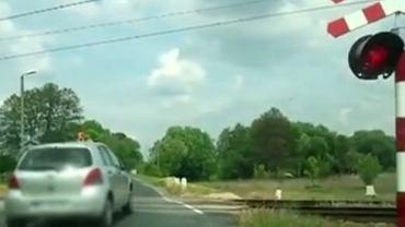 Samochód przejeżdża przez przejazd kolejowy na czerwonym świetle