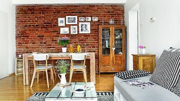 Do starej kamienicy pasują meble z historią - wyszukana wgliwickim sklepie zantykami witryna zzachowanymi kryształowymi przeszkleniami oraz wiekowa szafka nocna (dla przekory ustawiona wsalonie). Ceglana ściana to doskonałe miejsce na galerię rodzinnych zdjęć. Oświetlają ją halogeny wbudowane wpanel zpłyty gipsowo-kartonowej.