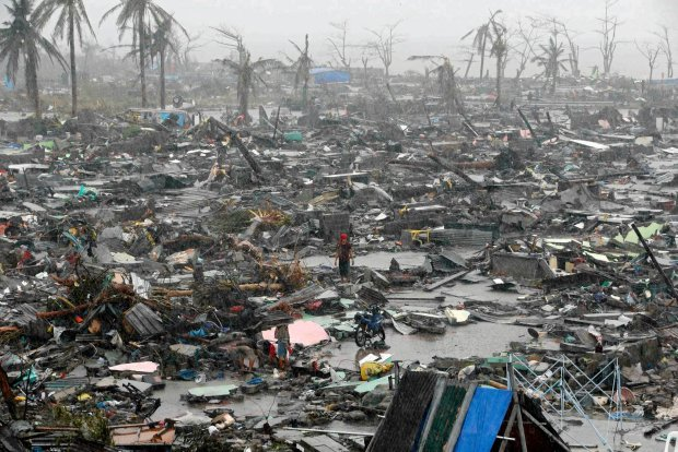 People stand among debris and ruins of houses destroyed after Super Typhoon Haiyan battered Tacloban city in central Philippines November 10, 2013. Haiyan, one of the most powerful storms ever recorded killed at least 10,000 people in the central Philippines province of Leyte, a senior police official said on Sunday, with coastal towns and the regional capital devastated by huge waves. Super typhoon Haiyan destroyed about 70 to 80 percent of the area in its path as it tore through the province on Friday, said chief superintendent Elmer Soria, a regional police director.   REUTERS/Erik De Castro (PHILIPPINES - Tags: DISASTER ENVIRONMENT TPX IMAGES OF THE DAY) SLOWA KLUCZOWE: :rel:d:bm:GF2E9BA0DA301