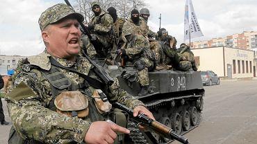 Prorosyjski bojówkarz, w tle inni separatyści na transporterze opancerzonym