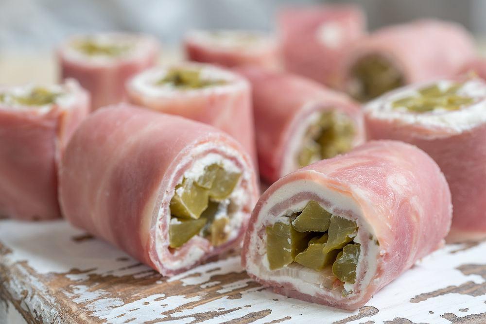 Przekąski do wódki - ruloniki z szynki konserwowej z czosnkowym serkiem i ogórkami kiszonymi (zdjęcie ilustracyjne)