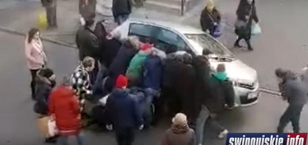 Świadkowie wypadku podnieśli samochód, by pomóc potrąconej starszej kobiecie.