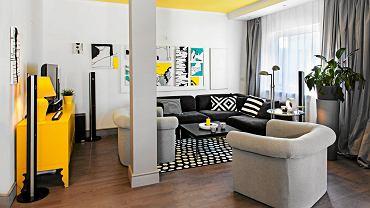 <B>W mieszkaniu młodych projektantów Zuzanny i Eryka w oczy rzucają się cztery kolory. Czwarty to jaskrawy żółty, któremu towarzyszy biel, czerń i szarość. I właśnie żółty miał w koncepcji wystroju grać pierwsze skrzypce. I tak się stało, gdy na tę barwę pomalowano sufity.</B> <BR />Aby powiększyć strefę dzienną, wyburzono ściany  - pozostał po nich słup konstrukcyjny. Pomalowano go na szaro, by jak najmniej rzucał się w oczy. Barwa ta nawiązuje do koloru zasłon. Ścianę za narożnikiem zdobią obrazy pani domu Zuzanny Lesińskiej.