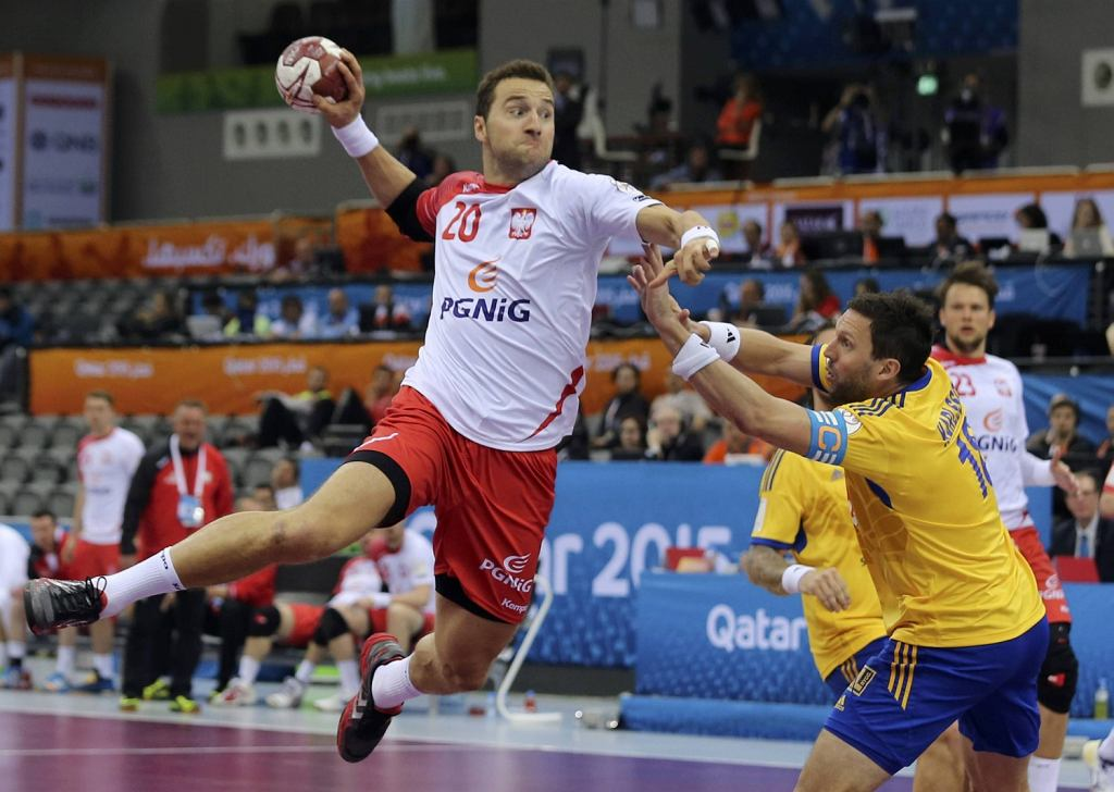 Jurkiewicz of Poland attempts to score past Karlsson of Sweden during their round of 16 match of the 24th mens handball World Championship in Doha