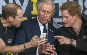 Mandatory Credit: Photo by Rupert Hartley/REX (4103574b)  Prince William and Prince Harry share something funny on an iPhone with their father Prince Charles  Invictus Games, Lee Valley Athletics Centre, London, Britain - 11 Sep 2014