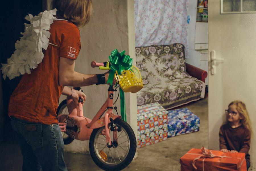 Wolontariusz wręcza rowerek dla dziewczynki