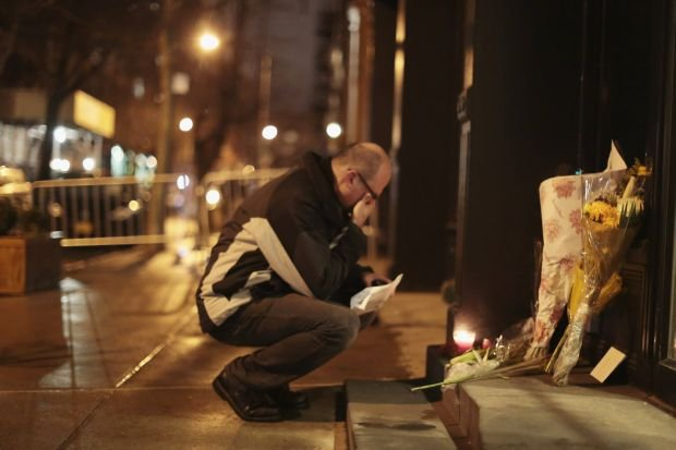 A man mourns in front of flowers placed in memory of actor Philip Seymour Hoffman outside the apartment where Hoffman was found dead in Manhattan, New York February 2, 2014. Hoffman, one of the leading actors of his generation, who won an Academy Award for his title role in the film