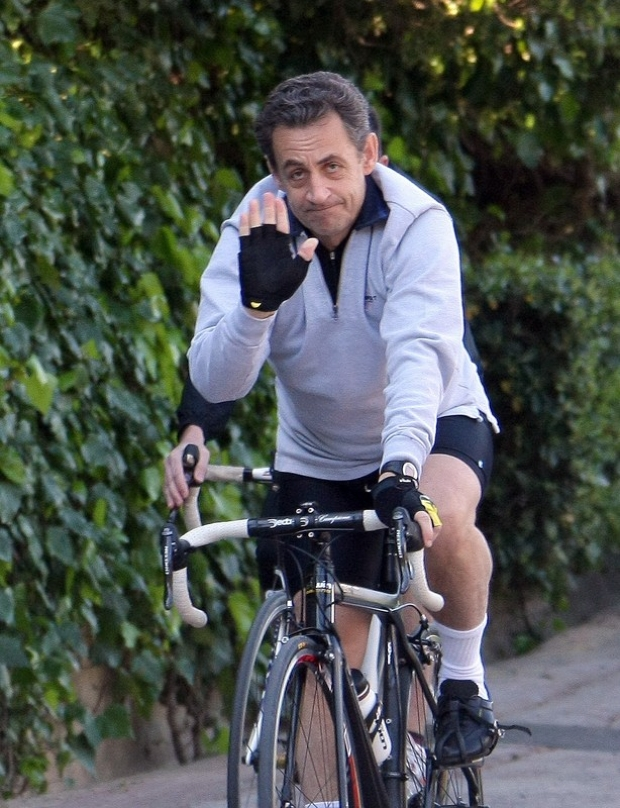 France's President and candidate for the Presidential Election 2012, waves as he rides his bicycle in Cavaliere, French Riviera, Sunday, April 8, 2012. Sarkozy and his wife, Carla Bruni-Sarkozy, are spending their Easter week-end at his mother-in-law's property in Cap Negre . (AP Photo/Claude Paris)